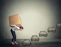Έννοια δύσκολου έργου Γυναίκα που φέρνει το βαρύ κιβώτιο επάνω Στοκ Εικόνες