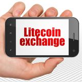 Έννοια Blockchain: Εκμετάλλευση Smartphone χεριών με την ανταλλαγή Litecoin στην επίδειξη στοκ φωτογραφία με δικαίωμα ελεύθερης χρήσης