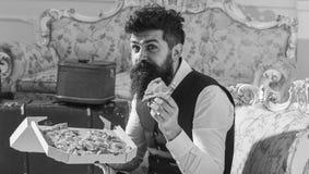 Έννοια Bon appetit Ο φαλλοκράτης στα κλασικά ενδύματα πεινασμένα, κρατά τη φέτα της πίτσας τυριών, τρώει, απολαμβάνοντας το γούστ Στοκ εικόνες με δικαίωμα ελεύθερης χρήσης