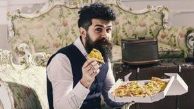 Έννοια Bon appetit Ο φαλλοκράτης στα κλασικά ενδύματα πεινασμένα, κρατά τη φέτα της πίτσας τυριών, τρώει, απολαμβάνοντας το γούστ Στοκ εικόνα με δικαίωμα ελεύθερης χρήσης