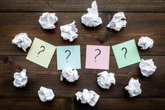 Έννοια FAQ Το ερωτηματικό στις κολλώδεις σημειώσεις τσαλάκωσε πλησίον το έγγραφο για τη σκοτεινή ξύλινη τοπ άποψη υποβάθρου στοκ φωτογραφίες