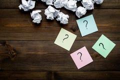 Έννοια FAQ Το ερωτηματικό στις κολλώδεις σημειώσεις τσαλάκωσε πλησίον το έγγραφο για το σκοτεινό ξύλινο διάστημα αντιγράφων άποψη στοκ εικόνα με δικαίωμα ελεύθερης χρήσης