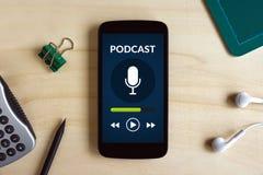 Έννοια Podcast στην έξυπνη τηλεφωνική οθόνη στο ξύλινο γραφείο Στοκ Εικόνες