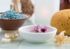 Έννοια SPA με το επιπλέοντα άλας λουτρών λουλουδιών και το σφουγγάρι λουτρών Στοκ Εικόνα