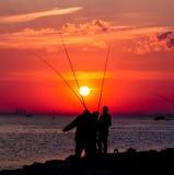 Έντονες κόκκινες σκιαγραφίες ηλιοβασιλέματος και ψαράδων Στοκ Φωτογραφία