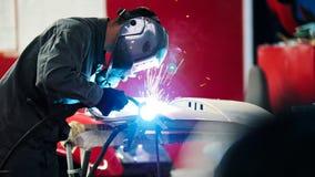Ένωση βιομηχανική: εργαζόμενος με λεπτομέρειες επισκευής κρανών στην αυτόματη υπηρεσία αυτοκινήτων - μπλε sparklers Στοκ εικόνα με δικαίωμα ελεύθερης χρήσης