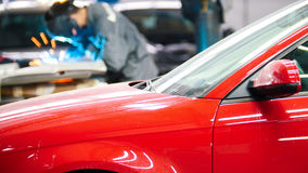 Ένωση βιομηχανική: εργαζόμενος με λεπτομέρειες επισκευής κρανών στην αυτόματη υπηρεσία μπροστά από το κόκκινο αυτοκίνητο Στοκ Φωτογραφίες