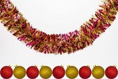 Ένωση ζωηρόχρωμου tinsel με τα κόκκινα και χρυσά μπιχλιμπίδια Χριστουγέννων, που απομονώνονται σε ένα άσπρο υπόβαθρο με το διάστη στοκ φωτογραφία με δικαίωμα ελεύθερης χρήσης