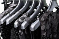 Ένωση ιματισμού μαύρων γυναικών στο μαύρο πλαστικό horizo κρεμαστρών Στοκ Φωτογραφίες