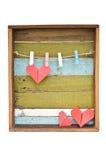 Ένωση καρδιών εγγράφου στη σκοινί για άπλωμα. Στην παλαιά ξύλινη ανασκόπηση. στοκ εικόνες