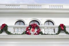 Ένωση στεφανιών και γιρλαντών Χριστουγέννων από ένα άσπρο μέγαρο στοκ εικόνες