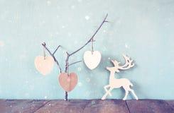 Ένωση της ξύλινης διακόσμησης raindeer καρδιών overand ξύλινης πέρα από το ξύλινο υπόβαθρο αναδρομική φιλτραρισμένη εικόνα Στοκ Εικόνες