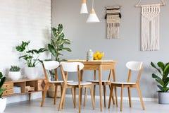 Ένωση Macrame στον γκρίζο τοίχο επάνω από τον ξύλινο πίνακα και τις καρέκλες στο BR στοκ φωτογραφία με δικαίωμα ελεύθερης χρήσης