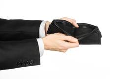 Ένδεια και θέμα χρημάτων: ένα άτομο σε ένα μαύρο κοστούμι που κρατά ένα κενό πορτοφόλι απομονωμένο στο άσπρο υπόβαθρο στο στούντι Στοκ φωτογραφία με δικαίωμα ελεύθερης χρήσης