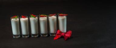 Έξι άσπρα ποτά καρύδων που διακοσμούνται με το κόκκινο και πράσινο λι πιπεριών Στοκ Εικόνες