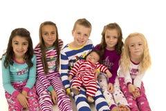Έξι λατρευτά παιδιά που φορούν το χαμόγελο πυτζαμών Χριστουγέννων ευτυχές στοκ εικόνες