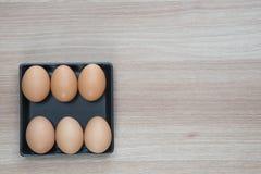 Έξι αυγά στο μαύρο πιάτο στην ξύλινη επιφάνεια με το διάστημα για το κείμενο Στοκ Εικόνες