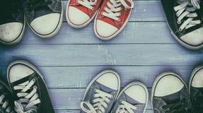Έξι ζευγάρια των παλαιών, φορεμένων πάνινων παπουτσιών σε μια ιώδη ξύλινη επιφάνεια στοκ εικόνα