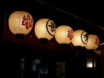 Έξι παραδοσιακά ιαπωνικά φανάρια εγγράφου που κρεμούν έξω από ένα εστιατόριο στο Κιότο στοκ εικόνες