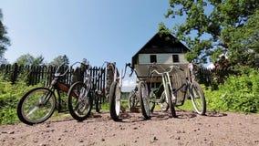 Έξι ποδήλατα μπροστά από τις ανοικτές πύλες και μεγάλο μέγαρο στην επαρχία δέντρο πεδίων απόθεμα βίντεο