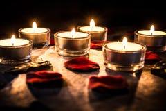 Έξι ρομαντικό Tealights στην πλάκα με τα ροδαλά πέταλα και βγάζουν φύλλα Στοκ Φωτογραφίες