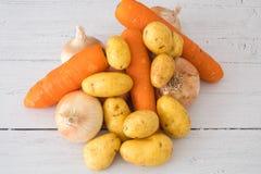 Έξι χρυσά σκωτσέζικα αυξημένα κρεμμύδια, μερικές πατάτες και τρία καρότα ένα από πέντε σας ημερησίως στην υγιή κατανάλωση στοκ εικόνα