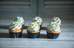 Έξι cupcakes με την άσπρη και μπλε κρέμα Στοκ Φωτογραφία