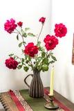 Έξοχη επίδειξη των κόκκινων λουλουδιών αίματος με έναν επιτραπέζιο δρομέα, και κερί Στοκ Εικόνα