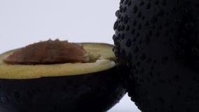 Έξοχη στενή μακροεντολή ενός ενός δαμάσκηνου μισού με ένα κοίλωμα Απελευθερώσεις νερού Περιστροφή στην περιστροφική πλάκα απομονω απόθεμα βίντεο