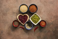 Έξοχοι δημητριακά τροφίμων, όσπρια, σπόροι και πιπέρια τσίλι σε ένα καφετί υπόβαθρο Chia, quinoa, φασόλια, φαγόπυρο, φακές, σουσά στοκ φωτογραφίες