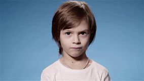 Έξοχος σε αργή κίνηση ενός χαριτωμένου μικρού παιδιού που εξετάζει τη κάμερα, μπλε υπόβαθρο απόθεμα βίντεο