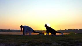 Έξοχο ηλιοβασίλεμα και κορίτσια που κάνουν μπροστινά Lunges σε μια γραφική τράπεζα λιμνών στην slo-Mo φιλμ μικρού μήκους