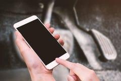 Έξυπνα τηλέφωνο λαβής γυναικών και κουμπί αφής με το χέρι με την κενή οθόνη για τη διαφήμιση, τον επιταχυντή και το φρένο του υπο στοκ φωτογραφία με δικαίωμα ελεύθερης χρήσης