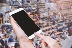 Έξυπνα τηλέφωνο λαβής γυναικών και κουμπί αφής με το χέρι με την κενή οθόνη για τη διαφήμιση, το στάδιο και το υπόβαθρο ακροατηρί στοκ φωτογραφία με δικαίωμα ελεύθερης χρήσης
