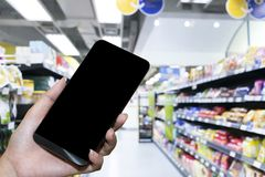 Έξυπνες τηλεφωνικές σε απευθείας σύνδεση αγορές στο χέρι γυναικών στοκ εικόνα