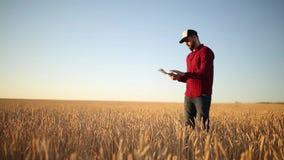 Έξυπνες χρησιμοποιώντας σύγχρονες τεχνολογίες καλλιέργειας στη γεωργία Ο αγρότης γεωπόνων κρατά την ψηφιακή επίδειξη υπολογιστών  φιλμ μικρού μήκους