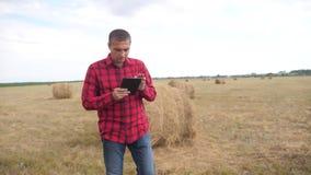Έξυπνη έννοια γεωργίας καλλιέργειας Τρόπος ζωής αγροτών ατόμων που μελετά μια θυμωνιά χόρτου σε έναν τομέα στην ψηφιακή ταμπλέτα  φιλμ μικρού μήκους