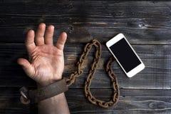 Έξυπνη έννοια τηλεφωνικού εθισμού στο κόκκινο υπόβαθρο Το χέρι δένεται με χειροπέδες στο smartphone στοκ φωτογραφία με δικαίωμα ελεύθερης χρήσης