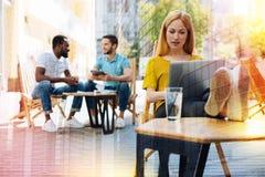 Έξυπνη γυναίκα που εργάζεται στο lap-top ενώ οι φίλοι της που κάθονται πίσω από την Στοκ Εικόνες