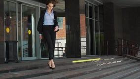 Έξυπνη επιχειρησιακή γυναίκα πόλεων που περπατά κοντά στο τεράστιο επιχειρησιακό κέντρο απόθεμα βίντεο