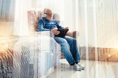 Έξυπνη ηλικίας συνεδρίαση ατόμων με μια ταμπλέτα και άκουσμα τη μουσική Στοκ Φωτογραφία