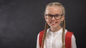 Έξυπνη μαθήτρια eyeglasses που χαμογελά στη κάμερα, δίψα για την εκπαίδευση γνώσης απόθεμα βίντεο