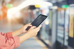Έξυπνη συσκευή ταμπλετών εκμετάλλευσης χεριών γυναικών στο τραίνο ουρανού BTS στο υπόβαθρο της Μπανγκόκ, Ταϊλάνδη, έννοια τεχνολο στοκ εικόνες