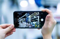 Έξυπνη φωτογραφία τηλεφωνικών βλαστών χρήσης χεριών γυναικών του ρομπότ στο βιομηχανικό EXPO Διεθνές γεγονός τεχνολογίας επεξεργα στοκ εικόνες