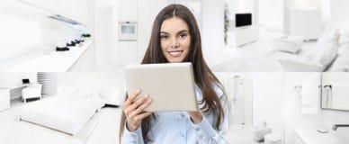 Έξυπνη χαμογελώντας γυναίκα έννοιας εγχώριου ελέγχου με την ψηφιακή ταμπλέτα επάνω στοκ εικόνα