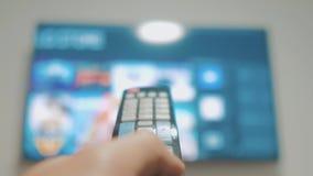 Έξυπνη TV με τα apps και το χέρι Το αρσενικό χέρι που κρατά τον τηλεχειρισμό κλείνει την έξυπνη TV εκμετάλλευση TV ελέγχων χεριών απόθεμα βίντεο