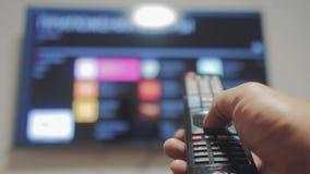 Έξυπνη TV με τα apps και το χέρι Το αρσενικό χέρι που κρατά τον τηλεχειρισμό κλείνει την έξυπνη TV TV τρόπου ζωής ελέγχων χεριών  απόθεμα βίντεο