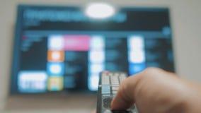 Έξυπνη TV με τα apps και το χέρι Το αρσενικό χέρι που κρατά τον τηλεχειρισμό κλείνει την έξυπνη TV εκμετάλλευση TV ελέγχων χεριών φιλμ μικρού μήκους