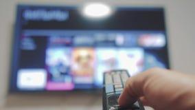 Έξυπνη TV με τα apps και το χέρι Ο αρσενικός τρόπος ζωής εκμετάλλευσης χεριών ο τηλεχειρισμός κλείνει τον έξυπνο τρόπο ζωής TV πό απόθεμα βίντεο