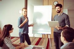 Έξυπνοι νέοι συνάδελφοι που στέκονται κοντά στο flipchart Στοκ Φωτογραφίες